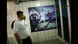 En esta foto del 27 de mayo de 2019, un jugador del equipo de fútbol masculino Bigtboys de personas transgénero pasa junto a un cartel de las estrellas del fútbol Neymar, Ronaldo y Messi, dentro de un vestuario en Rio de Janeiro, Brasil. (AP Foto / Silvia Izquierdo)