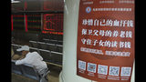 "A Chinese investor sits near a poster with the words ""Treasure your hard earned money, Protect your parent's retirement fund, Defend your children's education fund"" at a brokerage in Beijing Wednesday, June 12, 2019. Shares were mostly lower in Asia on Wednesday and Hong Kong's Seng index tumbled 1.7% as thousands continued protests against proposed legislation that many city residents fear could further erode the territory's legal autonomy. (AP Photo/Ng Han Guan)"
