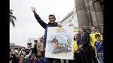 El ciclista ecuatoriano Richard Carapaz sostiene un dibujo de él durante un homenaje organizado por la municipalidad de Quito, el martes 11 de junio de 2019. (AP Foto/Dolores Ochoa)