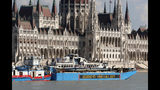 A barge carries the sightseeing boat past the house of parliament on the Danube river after it was lifted from riverbed in Budapest, Hungary, Tuesday, June 11, 2019. Four people are still missing from the May 29 collision between the Hableany (Mermaid) sightseeing boat and the Viking Sigyn river cruise ship near to Budapest's Margit Bridge. (AP Photo/Darko Bandic)