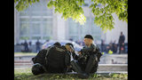 Riot policemen sit in the shade outside the presidency headquarters in Chisinau, Moldova, Wednesday, June 12, 2019. Moldova's police chief on Wednesday dismissed six officers who publicly backed a rival government, reflecting a continuing power struggle that has heightened political tensions in the impoverished ex-Soviet nation.(AP Photo/Roveliu Buga)
