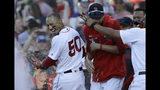 El jugador de los Medias Rojas de Boston, Mookie Betts (50), es bañado por sus compañeros luego de recibir la base por bolas con la casa llena que dio al equipo un triunfo 4-3 sobre los Rangers de Texas en Fenway Park, el miércoles 12 de junio de 2019, en Boston. (AP Foto/Elise Amendola)