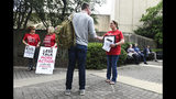 Jules Woodson, right, of Colorado Springs, Colo., hands out flyers while demonstrating outside the Southern Baptist Convention's annual meeting Tuesday, June 11, 2019, in Birmingham, Ala. First-time attendee Woodson spoke through tears as she described being abused sexually by a Southern Baptist minister. (AP Photo/Julie Bennett)