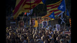 People hold independence flags and portraits of Catalan separatist leaders and activists jailed during a demonstration in downtown Barcelona, Spain, Wednesday, June 12, 2019. Catalan separatist leaders and activists told their Supreme Court trial on Wednesday they were exercising their democratic rights when they held a banned referendum on breaking away from Spain, denying charges of rebellion and sedition. (AP Photo/Emilio Morenatti)