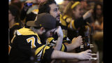 Boston Bruins fan Adam Aldred, front, of Foxborough, Mass., rests his head on his hand at a Boston bar, after the St. Louis Blues defeated the Bruins 4-1 in Game 7 of the NHL hockey Stanley Cup Final, Wednesday, June 12, 2019. (AP Photo/Steven Senne)