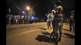 A man identified as Sonny Webber, right, father of Brandon Webber who was reportedly shot by U.S. Marshals earlier in the evening, joins a standoff as protesters take to the streets of the Frayser community in anger against the shooting, Wednesday, June 12, 2019, in Memphis, Tenn. (Jim Weber/Daily Memphian via AP)