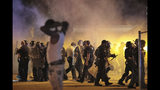 Police retreat under a cloud of tear gas as protesters disperse from the scene of a standoff after Frayser community residents took to the streets in anger against the shooting of a youth by U.S. Marshals earlier in the evening, Wednesday, June 12, 2019, in Memphis, Tenn. (Jim Weber/Daily Memphian via AP)