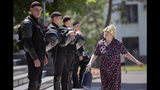 An elderly woman walks by a line of riot policemen standing outside the government headquarters in Chisinau, Moldova, Wednesday, June 12, 2019. Moldova's police chief on Wednesday dismissed six officers who publicly backed a rival government, reflecting a continuing power struggle that has heightened political tensions in the impoverished ex-Soviet nation.(AP Photo/Roveliu Buga)