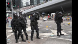 FILE - In this file photo taken Wednesday, June 12, 2019, a policeman fires with a pepper ball gun towards protesters near the Legislative Council in Hong Kong. Hong Kong police have resorted to harsher-than-usual tactics to suppress protesters this week in the city's most violent turmoil in decades. Police fired rubber bullets and beanbag rounds at the crowds, weapons that have not been widely used in recent history. (AP Photo/Kin Cheung, File)