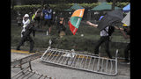FILE - In this file photo taken Wednesday, June 12, 2019, a police officer sprays pepper spray at protesters using an umbrella for protection near the Legislative Council in Hong Kong. Hong Kong police have resorted to harsher-than-usual tactics to suppress protesters this week in the city's most violent turmoil in decades. Police fired rubber bullets and beanbag rounds at the crowds, weapons that have not been widely used in recent history. (AP Photo/Kin Cheung, File)