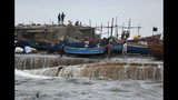People move a fishing boat to a safer ground on the Arabian Sea coast in Veraval, Gujarat, India, Wednesday, June 12, 2019. Indian authorities evacuated tens of thousands of people on Wednesday as a severe cyclone in the Arabian Sea approached the western state of Gujarat, lashing the coast with high winds and heavy rainfall. (AP Photo/Ajit Solanki)