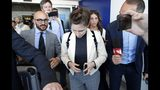 Amanda Knox, center, is approached by journalists upon her arrival in Linate airport, Milan, Italy, Thursday, June 13, 2019. Knox has returned to Italy for the first time since she was convicted and imprisoned, but ultimately acquitted, for the murder and sexual assault of her British roommate Meredith Kercher in the university town of Perugia in 2007. Knox is in Italy to attend a conference in Modena organized by the Italy Innocence Project, which seeks to help people who have been convicted for crimes they did not commit. (AP Photo/Antonio Calanni)