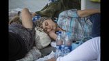 Supporters of the former government sleep outside the prosecutors office in Chisinau, Moldova, Wednesday, June 12, 2019. Moldova's police chief on Wednesday dismissed six officers who publicly backed a rival government, reflecting a continuing power struggle that has heightened political tensions in the impoverished ex-Soviet nation.(AP Photo/Roveliu Buga)