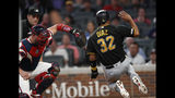 Pittsburgh Pirates' Elias Diaz (32) beats the tag from Atlanta Braves catcher Tyler Flowers to score on a Kevin Newman two-run double during the fourth inning of a baseball game Wednesday, June 12, 2019, in Atlanta. (AP Photo/John Bazemore)