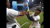 Atlanta Braves' Ozzie Albies, right, is doused by Ronald Acuna Jr., after driving in the winning run with a double in the 11th inning of a baseball game against the Pittsburgh Pirates early Thursday, June 13, 2019, in Atlanta. The Braves won 8-7. (AP Photo/John Bazemore)