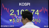 A currency trader walks by the screen showing the Korea Composite Stock Price Index (KOSPI) at the foreign exchange dealing room in Seoul, South Korea, Thursday, June 13, 2019. Asian stocks were mixed on Thursday as protesters in Hong Kong vowed to keep opposing a proposed extradition bill they fear would whittle down the territory's legal autonomy. (AP Photo/Lee Jin-man)