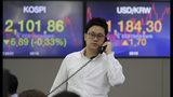 A currency trader talks on the phone near the screens showing the Korea Composite Stock Price Index (KOSPI), left, and the foreign exchange rate between U.S. dollar and South Korean won at the foreign exchange dealing room in Seoul, South Korea, Thursday, June 13, 2019. Asian stocks were mixed on Thursday as protesters in Hong Kong vowed to keep opposing a proposed extradition bill they fear would whittle down the territory's legal autonomy. (AP Photo/Lee Jin-man)