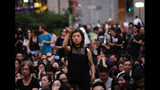 A woman holds a flower as she joins hundreds of mothers protesting against the amendments to the extradition law after Wednesday's violent protest in Hong Kong on Friday, June 14, 2019. Calm appeared to have returned to Hong Kong after days of protests by students and human rights activists opposed to a bill that would allow suspects to be tried in mainland Chinese courts. (AP Photo/Vincent Yu)