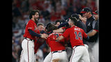 Atlanta Braves mob Brian McCann after he hit a two-run single in the ninth inning of a baseball game to defeat Philadelphia Phillies 9-8 Friday, June 14, 2019, in Atlanta. (AP Photo/John Bazemore)