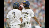Michigan's Jesse Franklin (7) and Jordan Brewer (22) celebrate after scoring on Jimmy Kerr's two-run triple against Texas Tech in the third inning of an NCAA College World Series baseball game in Omaha, Neb., Saturday, June 15, 2019. (AP Photo/Nati Harnik)