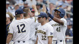 Michigan's Jordan Nwogu (42) celebrates after scoring against Texas Tech on a sacrifice fly by Jordan Brewer, in the first inning of an NCAA College World Series baseball game in Omaha, Neb., Saturday, June 15, 2019. (AP Photo/Nati Harnik)