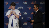 Marc Tramuta, right, New York Mets director of amateur scouting, looks on as Mets 2019 first round pick Brett Baty, a third baseman from Lake Travis High School in Austin, Texas, who was drafted 12th overall, buttons on a jersey during a news conference after Baty signed with the team prior to a baseball game against the St. Louis Cardinals, Saturday, June 15, 2019, in New York. (AP Photo/Julio Cortez)
