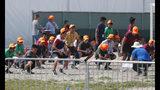 ARCHIVO - En esta fotografía de archivo del 6 de mayo de 2019, niños migrantes hacen ejercicio afuera del Albergue Temporal para Niños Sin Acompañante en Homestead, Florida. (AP Foto/Wilfredo Lee, archivo)