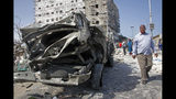 A man walks past the wreckage of an official vehicle that was destroyed in a bomb attack in the capital Mogadishu, Somalia, Saturday, June 15, 2019. (AP Photo/Farah Abdi Warsameh)