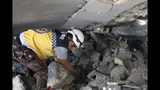 This photo posted and provided by the Syrian Civil Defense White Helmets, which has been authenticated based on its contents and other AP reporting, shows a Civil Defense worker searching for victims under the rubble after an airstrike by Syrian government forces hit the town of Maaret al-Numan in Idlib province, Syria, Saturday, June. 15, 2019. Syrian opposition activists say government airstrikes on rebel-held areas in northwestern Syrian and intense fighting claimed the lives dozens of people. (Syrian Civil Defense White Helmets via AP)