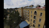 In this Friday, April 19, 2019 photo, the Ledra Palace Hotel is seen from the roof inside the U.N. buffer zone in the divided capital Nicosia, Cyprus. This grand hotel still manages to hold onto a flicker of its old majesty despite the mortal shell craters and bullet holes scarring its sandstone facade. Amid war in the summer of 1974 that cleaved Cyprus along ethnic lines, United Nations peacekeepers took over the Ledra Palace Hotel and instantly turned it into an emblem of the east Mediterranean island nation's division. (AP Photo/Petros Karadjias)