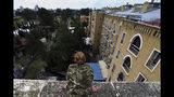 In this Friday, April 19, 2019, photo, a U.N. peacekeeper looks down at the grounds of the Ledra Palace hotel from the roof in the divided capital Nicosia, Cyprus. This grand hotel still manages to hold onto a flicker of its old majesty despite the mortal shell craters and bullet holes scarring its sandstone facade. Amid war in the summer of 1974 that cleaved Cyprus along ethnic lines, United Nations peacekeepers took over the Ledra Palace Hotel and instantly turned it into an emblem of the east Mediterranean island nation's division. (AP Photo/Petros Karadjias)