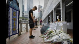 A man pays respect on the site where a man fell to his death a day earlier after hanging a protest banner against the extradition bill on the scaffolding of a shopping mall in Hong Kong, Sunday, June 16, 2019. Hong Kong was bracing Sunday for another massive protest over an unpopular extradition bill that has highlighted the territory's apprehension about relations with mainland China, a week after the crisis brought as many as 1 million into the streets. (AP Photo/Vincent Yu)