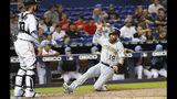 Colin Moran (19), de los Piratas de Pittsburgh, se barre para anotar en el cuarto inning del partido frente a los Marlins de Miami, el domingo 16 de junio de 2019, en Miami. (AP Foto/Wilfredo Lee)