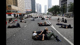 Protesters who camped out overnight take a rest along a main road near the Legislative Council after continuing protest against the unpopular extradition bill in Hong Kong, Monday, June 17, 2019. Hong Kong police and protesters faced off Monday as authorities began trying to clear the streets of a few hundred who remained near the city government headquarters after massive demonstrations that stretched deep into the night before. (AP Photo/Vincent Yu)