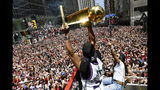 Toronto Raptors guard Kyle Lowry holds the Larry O'Brien Championship Trophy up for the fans during the NBA basketball championship team's victory parade in Toronto, Monday, June 17, 2019. (Frank Gunn/The Canadian Press via AP)
