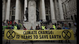 """FILE - In this Thursday, April 25, 2019 file photo, Extinction Rebellion climate change protesters hold up a banner near the Bank of England, in the City of London. The environmental activist group Extinction Rebellion has postponed a plan to shut down London's Heathrow Airport with drones after it was criticized by politicians and police. The anti-climate change group said Sunday, June 16 it would """"not be carrying out any actions at Heathrow Airport in June or July."""" (AP Photo/Matt Dunham, file)"""