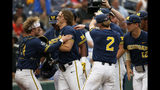 Michigan's Jesse Franklin, center left, is greeted at the dugout after he hit a solo home run against Florida State in the first inning of an NCAA College World Series baseball game in Omaha, Neb., Monday, June 17, 2019. (AP Photo/Nati Harnik)