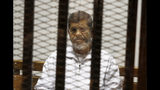 FILE - In this May 8, 2014 file photo, Egypt's ousted Islamist President Mohammed Morsi sits in a defendant cage in the Police Academy courthouse in Cairo, Egypt. On Monday June 17, 2019, Egypt's state TV said the country's ousted President Mohammed Morsi, 67, collapsed during a court session and died. It said it occurred while he was attending a court trial on espionage charges. Morsi, who hailed from Egypt's largest Islamist group, the now outlawed Muslim Brotherhood, was elected president in 2012 in the country's first free elections following the ouster the year before of longtime leader Hosni Mubarak. (AP Photo/Tarek el-Gabbas, File)