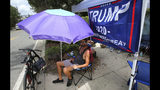 Ray Renaud, from Daytona Beach, Fla., is ready with a beach umbrella as supporters of President Donald Trump camp out in front of the Amway Center, Monday, June 17, 2019, ahead of Tuesday's 2020 campaign kick-off rally in Orlando, Fla. (Joe Burbank/Orlando Sentinel via AP)