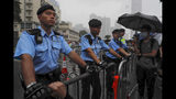 Policemen stand guard in the rain as protesters gather near the Legislative Council continuing protest against the unpopular extradition bill in Hong Kong, Monday, June 17, 2019. A member of Hong Kong's Executive Council says the city's leader plans to apologize again over her handling of a highly unpopular extradition bill. (AP Photo/Kin Cheung)