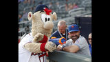 Atlanta Braves mascot Blooper takes aim at a New York Mets player in the dugout with a toy gun as Mets manager Mickey Callaway (36) looks on before a baseball game Monday, June 17, 2019, in Atlanta. (AP Photo/John Bazemore)