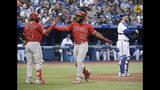 El jugador de los Angelinos de Los Ángeles, Brian Goodwin (18), celebra con su compañero, el venezolano Luis Rengifo (4), su jonrón ante el abridor de los Azulejos de Toronto, Marcus Stroman, durante el quinto inning de un juego de béisbol en Toronto, el martes 18 de junio de 2019. (Nathan Denette/The Canadian Press vía AP)