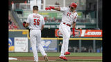 Cincinnati Reds' Derek Dietrich (22) celebrates with third base coach J.R. House (56) as he runs the bases after hitting a two-run home run off Houston Astros starting pitcher Justin Verlander during the first inning of a baseball game Tuesday, June 18, 2019, in Cincinnati. (AP Photo/John Minchillo)