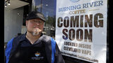 "Johnny Rowan stands outside Burning River Coffee, Friday, June 14, 2019, in Lakewood, Ohio. Rowan's is one of 90 active businesses registered with the state that have ""burning river"" in their names, inspired by the Cuyahoga River's most famous fire. (AP Photo/Tony Dejak)"