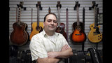 Jacob Tuel, owner of Burning River Guitars, poses for a photo in his workshop, Monday, June 10, 2019, in Akron, Ohio. Tuel named his guitar shop after the 1969 blaze on the Cuyahoga River, in Cleveland. (AP Photo/Tony Dejak)