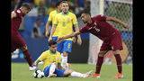 El venezolano Yangel Herrera (derecha) extiende la mano hacia el brasileño Philippe Coutinho (en el piso) durante el partido por el Grupo A de la Copa América en la Arena Fonte Nova en Salvador, Brasil, el martes 18 de junio de 2019. (AP Foto/Natacha Pisarenko)