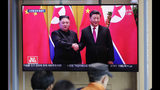People watch a TV news program reporting about Chinese President Xi Jinping's state visit to North Korea with file footage of Xi and North Korean leader Kim Jong Un at the Seoul Railway Station in Seoul, South Korea, Tuesday, June 18, 2019. (AP Photo/Lee Jin-man)