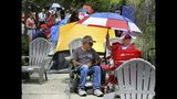James DeWilde and Laureen Vartanian, from Port Orange, Fla., use a patriotic-theme beach umbrella to stay cool as supporters of President Donald Trump camp out in front of the Amway Center, Monday, June 17, 2019, ahead of Tuesday's 2020 campaign kick-off rally in Orlando, Fla. (Joe Burbank/Orlando Sentinel via AP)