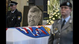 FILE-In this June 13, 2019 file photo a picture of Walter Luebcke stands behind his coffin during the funeral service in Kassel, Germany. German authorities say they have arrested a 45-year-old man in connection with their investigation into the slaying of a regional official from Chancellor Angela Merkel's party. (Swen Pfoertner/dpa via AP)
