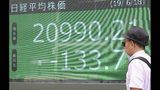 A man walks by an electronic stock board of a securities firm in Tokyo, Tuesday, June 18, 2019. Stocks in Asia mostly advanced Tuesday ahead of interest rate decisions by the U.S. Federal Reserve and other central banks. (AP Photo/Koji Sasahara)